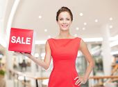 sale, shopping , christmas, holidays and people concept - smiling woman in red dress with sale sign over mall background