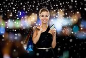 shopping, sale, banking, money and holidays concept - smiling woman in dress with shopping bags and credit card over black background