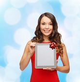 christmas, holidays, technology and people concept - smiling woman in red dress with tablet pc computer over blue lights background