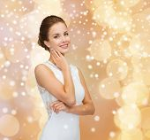 christmas, holidays, celebration, wedding and people concept - smiling woman in white dress wearing diamond earrings over beige lights background and snow