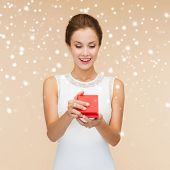 holidays, presents, wedding and happiness concept - smiling woman in white dress holding red gift box over beige background over beige background and snow
