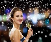 party, drinks, holidays, people and christmas concept - smiling woman in evening dress with glass of sparkling wine over night lights and snow background