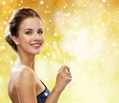 party, drinks, holidays, people and christmas concept - smiling woman in evening dress with glass of sparkling wine over yellow lights and snow background