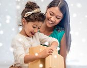 christmas, holidays, celebration, family and people concept - happy mother and child girl with gift box over snowy background