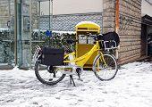Postal delivery in bike, in winter