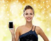 technology, christmas, advertisement and people concept - smiling woman in evening dress holding smartphone over yellow lights and snow background