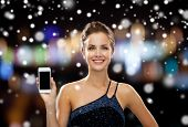 technology, christmas, holidays, advertising and people concept - smiling woman in evening dress holding smartphone over night lights and snow background