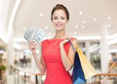 sale, money, people and holidays concept - smiling woman in red dress with shopping bags and dollars over mall background