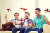 friendship, sports and entertainment concept - happy male friends with flags and vuvuzela supporting football team at home