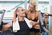 Smiling female trainer assisting man on fitness machine at the gym