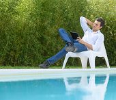 Man reading a tablet sitting by the pool