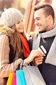 A picture of a beautiful couple shopping with a credit card in the city