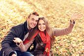 A picture of a happy couple relaxing in the autumn park