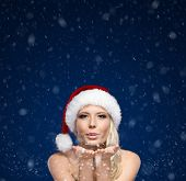 Attractive woman in Christmas cap blows kiss, blue snowy background