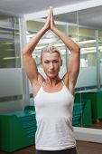 Portrait of a sporty young woman with joined hands over head at fitness studio