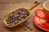 coffee beans on a rustic wooden scoop against grunge wood with stoneware cup