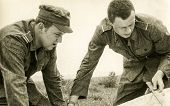 POLAND, CIRCA FIFTIES: Vintage photo of two soldiers reading a map during military training