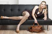 woman wearing pumps with a handbag lying on sofa