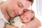 Young Father Tenderly Holding  Newborn