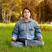 Bright picture. Young man meditating outdoors