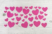 Many pink hearts on wooden shabby chic white background for valentines day or wedding greetings.