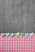 Shabby chic grey wooden background with hearts on a pink white checkered frame.
