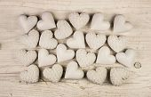 Beige or old white hearts on wooden shabby chic background for a greeting card.