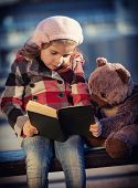 Little girl reads the book to a toy bear