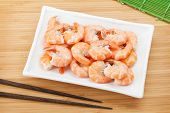 Cooked shrimps and chopsticks. View from above on wooden table