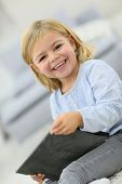 Cute little girl with tablet laughing outloud