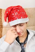 image of sad christmas  - Sad and Tired Teenager in Santa Hat on the Sofa at the Home - JPG