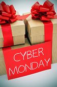 a pile of gifts and the text cyber monday written in white in a red signboard