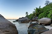 Old Boulders and Green Plants and Palm Trees at the Seaside of Mahe Island, Seychelles.
