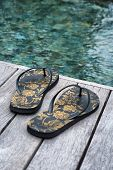 Close up Black Floral Flip Flops on Wooden Platform at the Edge of the Swimming Pool