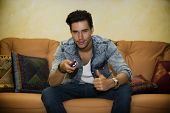 Young Man Sitting Watching Tv And Doing Ok Sign With Thumb Up