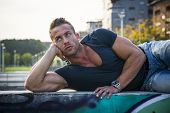 Handsome Muscular Blond Man Laying Down In City