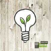 Green eco energy concept, plant growing inside the light bulb, on wooden texture.