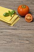 stock photo of lasagna  - Raw pasta lasagna with basil leaves and fresh tomatoes on wooden background - JPG