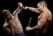 image of filipino  - two muscular martial artists sparring on a black background - JPG