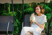 pic of swingset  - Woman drinks fresh coconut on the swinset - JPG