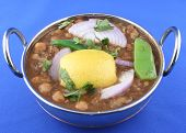 image of kadai  - traditional indian hot and spicy chick pea curry in a kadai garnished with lemon and green peppers - JPG
