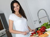 stock photo of model home  - Young Woman Cooking in the kitchen - JPG