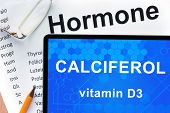 stock photo of hormones  - Papers with hormones list and tablet  with words Calciferol  - JPG