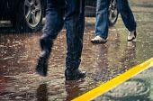 picture of wet feet  - male feet stepping on wet from rain sidewalk in a city - JPG