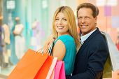 stock photo of mall  - Cheerful mature couple holding shopping bags and looking over shoulder while standing in shopping mall - JPG