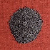 foto of opiate  - Top view of poppy seeds against red vinyl background. ** Note: Soft Focus at 100%, best at smaller sizes - JPG