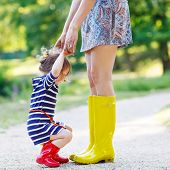image of little young child children girl toddler  - Young mother and little adorable child girl in rubber boots having fun together family look in summer park on sunny warm day - JPG