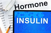 foto of hormones  - Papers with hormones list and tablet  with word  insulin - JPG