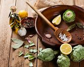 stock photo of artichoke hearts  - Preparing roast artichokes with spices and olive oil on a rustic wooden background  - JPG