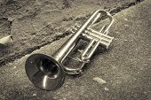 stock photo of trumpets  - Old worn trumpet stands alone in alleyway behind a jazz club - JPG